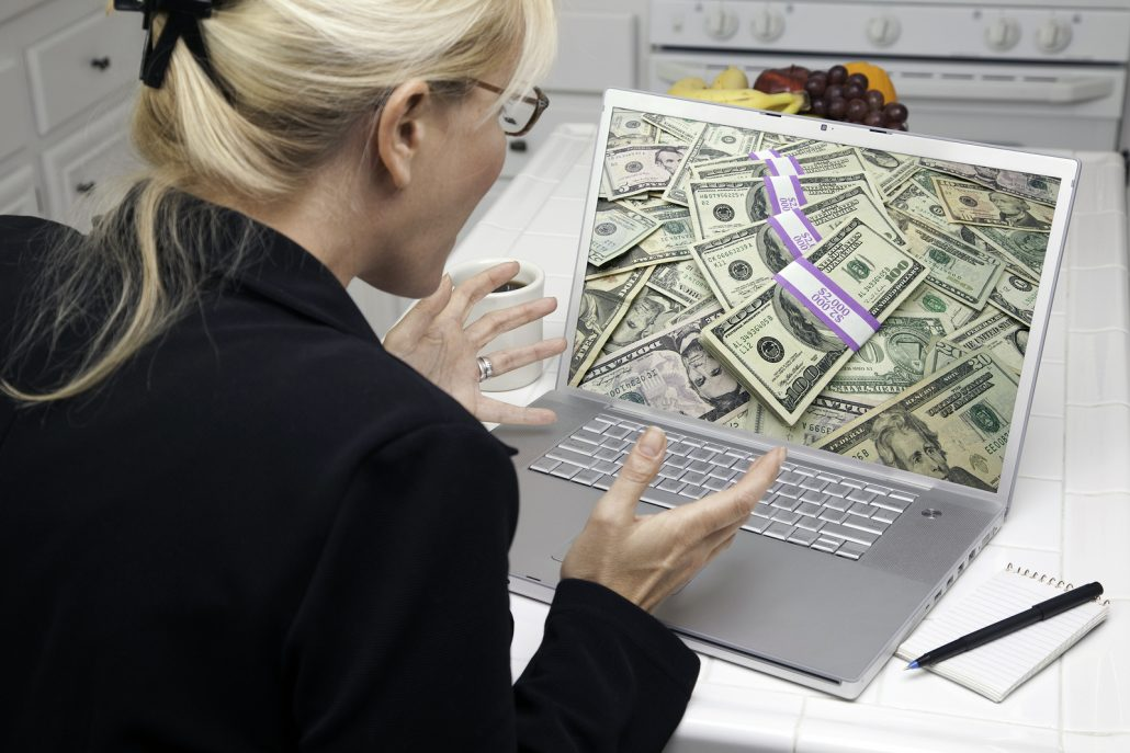 Excited Woman In Kitchen Using Laptop - Money