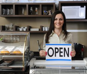 Happy Owner Of A Caf Showing Open Sign