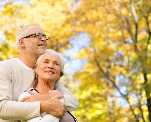 family, age, season and people concept - happy senior couple hug