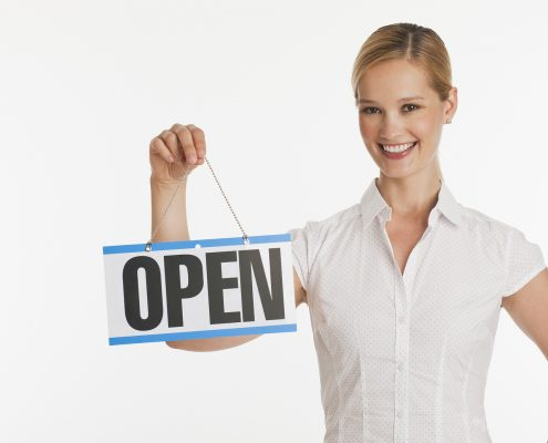 Female small business owner holding up Open sign with white seamless background